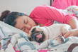 Asian Woman and her ugly pug dog sleep in the bed