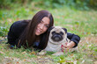girl and her best friend, pug lying on the grass
