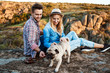 Young couple smiling, sitting on rock in canyon, stroking pug dog.
